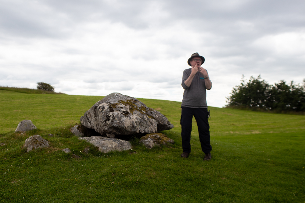 Patrick Meehan, tour guide extraordinaire, standing beside one of the many monuments at the Carrowmore megalithic site