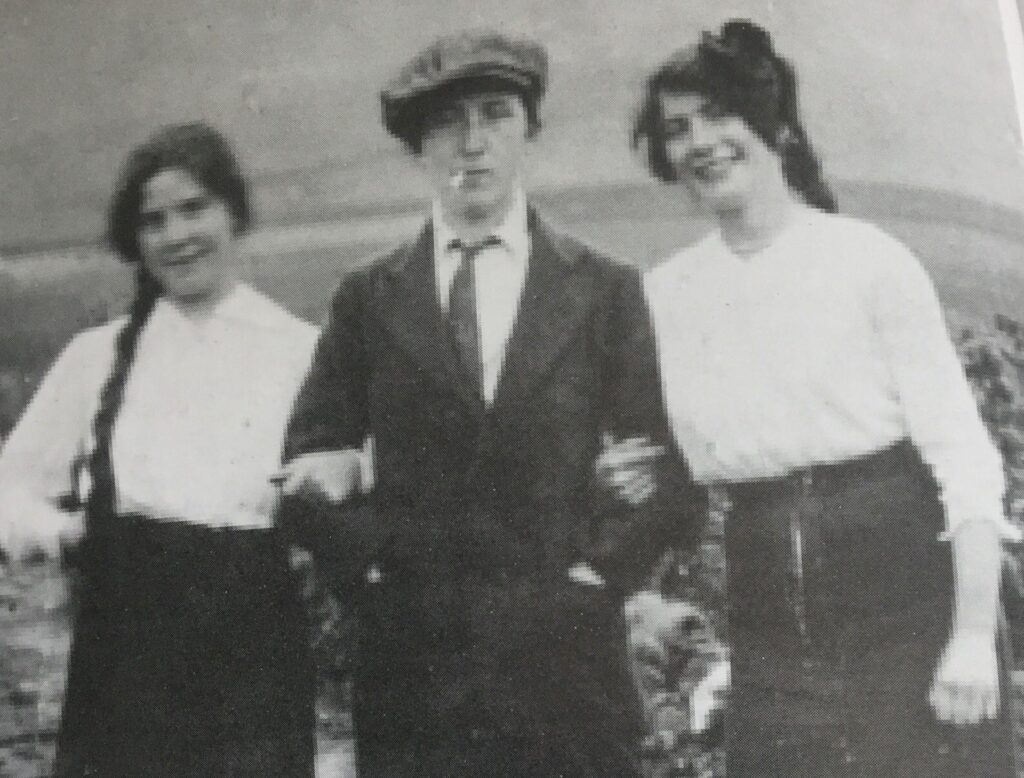 Margaret Skinnider pictured dressed as a man, with a woman on each arm