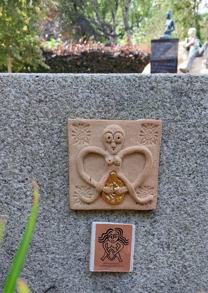 Ceramic Sheela na Gig plaque with gold vulva on a stone bench in Merrion Square, Her son Oscar's statue can be glimpsed in the background.