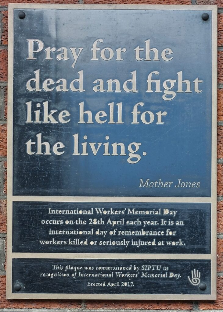 """Black rectangular plaque on brick wall.  Text reads """"Pray for the dead and fight like hell for the living"""". Mother Jones. International Workers' Memorial Day occurs on the 28th April each year, It is a day of remembrance for workers killed or seriously injured at work. Erected by SIPTU, April 2017."""
