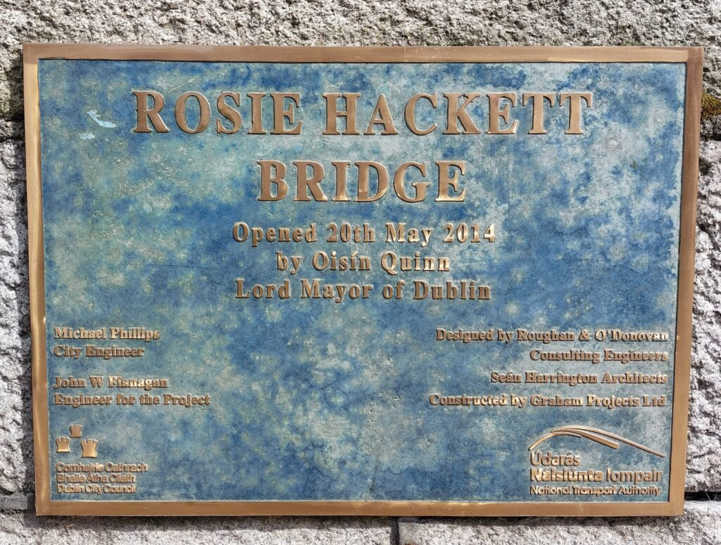 Rectangular metal plaque against a stone wall. Text in bronze reads Rosie Hackett bridge opened 20th May 2014 by Oisín Quinn, Lord Mayor of Dublin and a list of engineers, architects and construction firms involved in the project.
